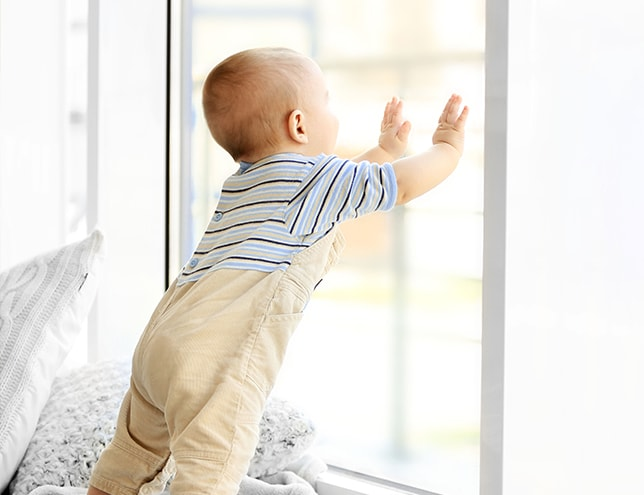 toddler leaning on a window