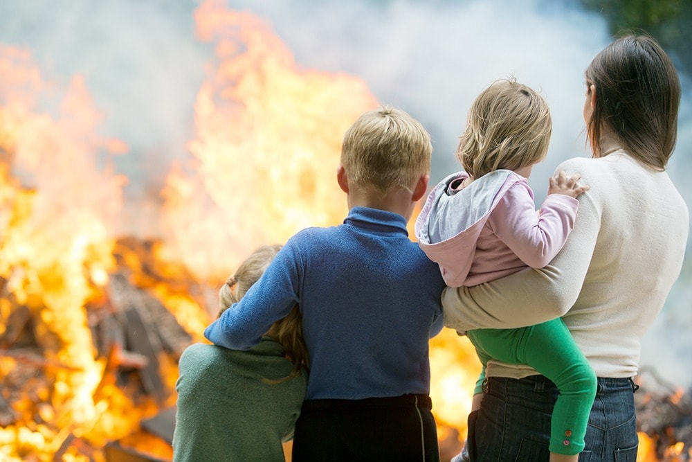 A mom with her 3 children watching their house on fire.