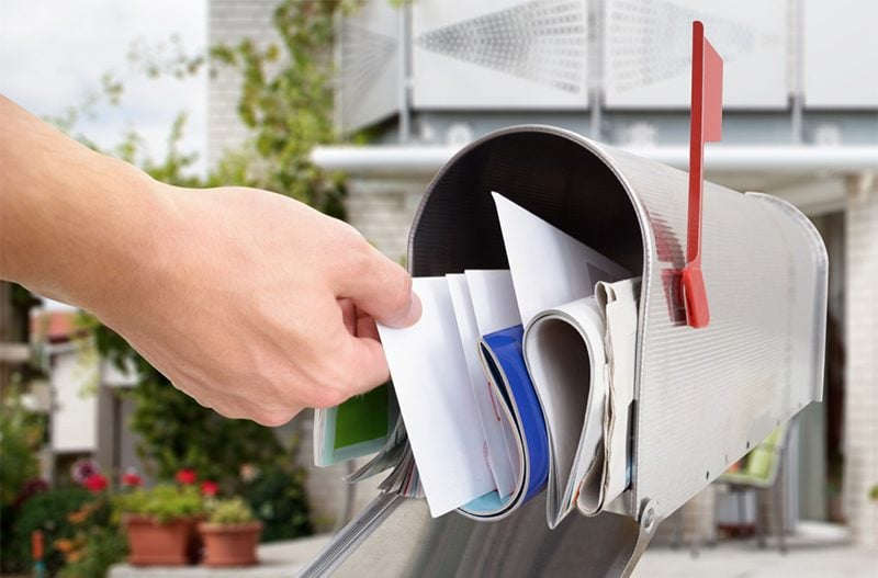 A hand getting a mail from the mailbox