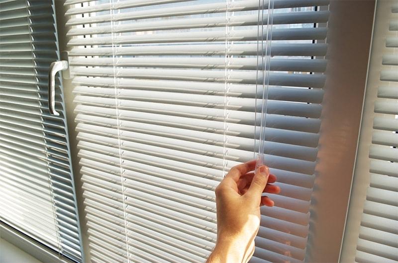 A hand closing window blinds.